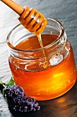 A jar of honey with a honey spoon and lavender flowers