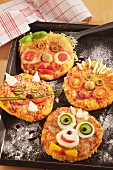 Mini pizzas with funny faces for a children's birthday party