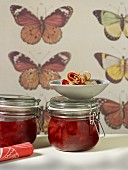 Two jars of strawberry jam and pancakes