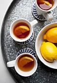 Three cups of lemon tea and fresh lemons