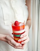A woman holding a glass of raspberry juice garnished with a fresh raspberry