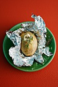 A baked potato with rosemary