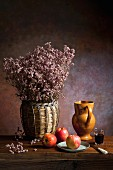 An arrangement featuring apples, dried flowers, an earthenware jug, wine and a knife