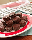 Chocolate cupcakes waiting to be decorated on a red and white plate