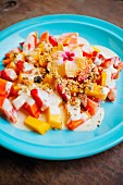 Fresh fruit with yogurt and muesli on a blue plate