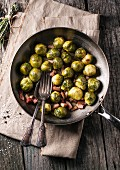 Fried Brussels sprouts with bacon in a pan on an old wooden table