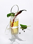 Oil, herbs, a chilli pepper and peppercorns