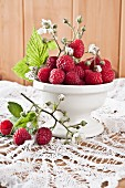 Raspberries with sprigs and flowers in a bowl