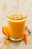 A carrot and orange smoothie in a glass