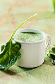 Spinach soup in an enamel mug