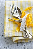 A place setting with a name tag and sunflower petals on a napkin