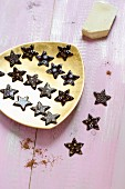 Dark chocolate stars with light decorations on a golden plate