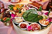 An oriental platter featuring chicken, prawns, cucumber, piri-piri, rice and peanuts