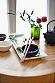 An oriental arrangement featuring a bowl, chopsticks, noodles and tea