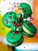 Green macaroons filled with a light cream and pomegranate seeds
