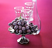 Red grapes on a silver platter with an empty carafe and glasses in the background
