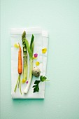 Spring vegetables with a quail's egg, parsley and edible flowers on a napkin
