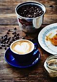 A cappuccino, coffee beans, sugar and a croissant