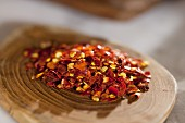A pile of chilli flakes on a wooden plate