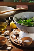 Fresh rocket in a colander with garlic, salt, pepper, lemon and olive oil