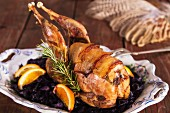 Pheasant wrapped in bacon with oranges and red cabbage