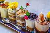 Various cream desserts iin glasses decorated with flowers