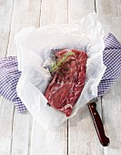 Saddle of young wild boar with black pepper and rosemary on a piece of paper