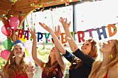 Four teenagers at a birthday party throwing confetti in the air