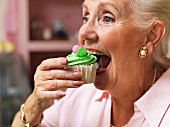 An old lady taking a big bite out of a cupcake