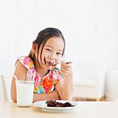 A little girl eating a slice of chocolate cake