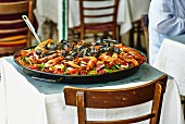 A pan of paella on a restaurant table