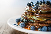 Blueberry Pancakes with Maple Syrup on a White Plate with a Spoon