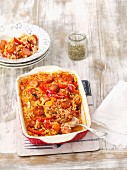 Rice bake with tomatoes, sausage, peppers, carrots and leek