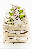 A layered dessert made with sponge fingers, cream cheese, chocolate and mint