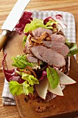 Country bread topped with roast wild boar, sliced apple and lettuce