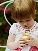A little girl holding an elderflower cupcake
