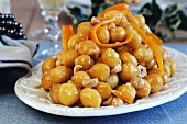 Stuffoli (fried dough balls dipped in honey with candied orange zest and hazelnuts, Italy)