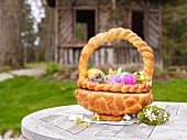 An Easter basket made from bread filled with Easter eggs on a garden table
