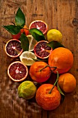 Blood oranges, mandarins and lemons on a wooden surface (seen from above)