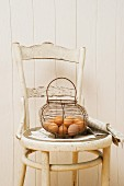 Eggs in a wire basket on an old-fashioned chair
