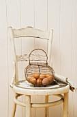 Eier im Drahtkorb auf Vintage-Stuhl