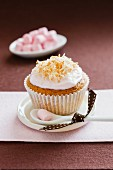A cupcake decorated with coconut cream and served with mini marshmallows