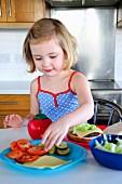 Kleines Mädchen belegt Hamburger mit Tomaten