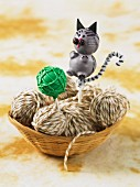 A cat-shaped cake pop in a basket of wool