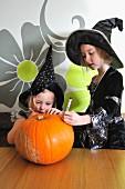 Zwei Mädchen in Halloween-Kostümen bemalen einen Kürbis