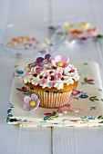 A cupcake decorated with sugar flowers