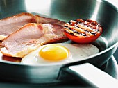 A fried egg, bacon and half a tomato in a pan