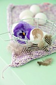 Egg shells, feathers and pansies in a wire basket
