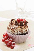 A cupcake decorated with chocolate letters and redcurrants