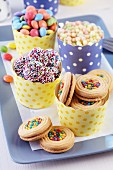 Gepunktete Papierförmchen mit bunten Keksen, Smarties und Puffreis auf Tablett serviert